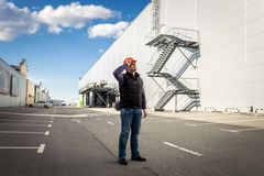 Male worker posing on parking of industrial building Royalty Free Stock Photo