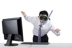 Male worker posing to swim. Strange businessman wearing goggles and snorkel with computer on desk, posing to swim Royalty Free Stock Photo
