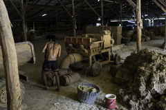 Male worker prepares clay for making pottery. A grinder is used to prepare fine clay. Feb 21, 2017 - Ratchaburi, Thailand: Male worker prepares clay for making Royalty Free Stock Photography