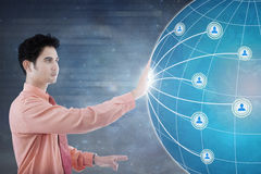 Male worker pressing social network interface. Concept of social network connection. Asian businessman pressing social network icon and globe on the futuristic Stock Photos