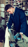 Male worker processing plank in machine at workshop Royalty Free Stock Photography