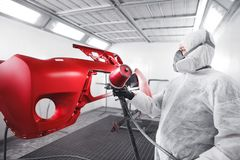 Male worker in protective clothes and mask painting car using spray paint. stock photos