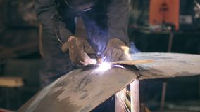 Male worker in protective gloves and workwear is cutting off metal piece with oxy acetylene cutting torch at a factory stock video footage