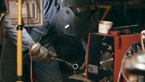 Male worker in protective glowes welds two metal pieces together at mechanical hangar. stock video footage