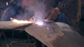 Male worker in protective workwear is cutting pieces off metal construction with oxy acetylene cutting torch stock video footage