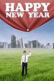 Male worker pulling new year text. Portrait of asian worker pulling a big banner with new year text outdoors Stock Photos