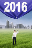 Male worker pulls banner with numbers 2016. Image of young businessman standing on the meadow while pulling a banner with numbers 2016 Royalty Free Stock Images