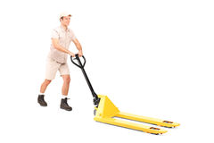 Male worker pushing a fork pallet truck Royalty Free Stock Photo