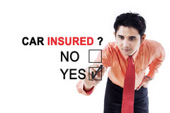 Male worker with question of car insured. Young male worker using a pen while choosing a yes option to a question of car insured on the whiteboard Stock Photography