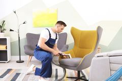 Male worker removing dirt from armchair. With professional vacuum cleaner indoors Royalty Free Stock Image