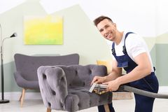 Male worker removing dirt from armchair. With professional vacuum cleaner indoors Stock Image