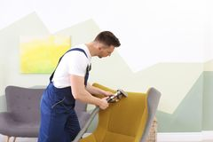 Male worker removing dirt from armchair. With professional vacuum cleaner indoors Stock Photography