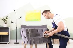 Male worker removing dirt from armchair. With professional vacuum cleaner indoors Stock Images