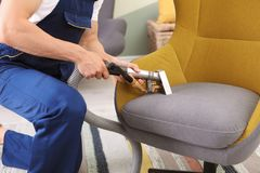 Male worker removing dirt from armchair. With professional vacuum cleaner indoors, closeup Royalty Free Stock Images