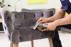 Male worker removing dirt from armchair. With professional vacuum cleaner indoors, closeup Stock Photos