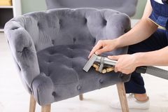 Male worker removing dirt from armchair with professional vacuum cleaner. Indoors, closeup Stock Photos