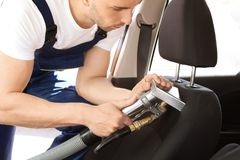 Male worker removing dirt from car seat. With professional vacuum cleaner Stock Image
