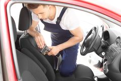Male worker removing dirt from car seat. With professional vacuum cleaner Stock Photos