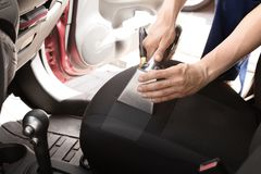 Male worker removing dirt from car seat. With professional vacuum cleaner Royalty Free Stock Photography