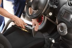 Male worker removing dirt from car seat. With professional vacuum cleaner Stock Photography