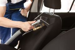 Male worker removing dirt from car seat. With professional vacuum cleaner Stock Images