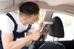 Male worker removing dirt from car seat. With professional vacuum cleaner Royalty Free Stock Images