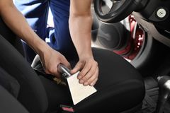 Worker removing dirt from car seat with professional vacuum cleaner. Male worker removing dirt from car seat with professional vacuum cleaner Stock Image