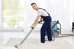 Male worker removing dirt from carpet. With professional vacuum cleaner indoors Royalty Free Stock Image