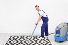 Male worker removing dirt from carpet. With professional vacuum cleaner indoors Stock Photos