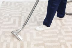 Male worker removing dirt from carpet. With professional vacuum cleaner indoors Royalty Free Stock Photos