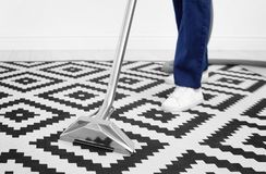 Male worker removing dirt from carpet. With professional vacuum cleaner indoors Royalty Free Stock Images