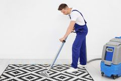 Male worker removing dirt from carpet. With professional vacuum cleaner indoors Stock Image