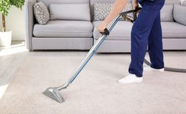 Male worker removing dirt from carpet. With professional vacuum cleaner indoors Stock Images
