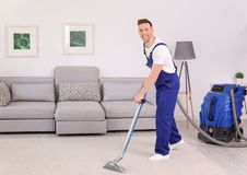 Male worker removing dirt from carpet. With professional vacuum cleaner indoors Royalty Free Stock Photography