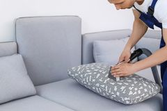 Male worker removing dirt from sofa. With professional vacuum cleaner indoors Royalty Free Stock Image