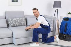 Male worker removing dirt from sofa. With professional vacuum cleaner indoors Stock Photography