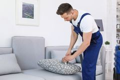 Male worker removing dirt from sofa. With professional vacuum cleaner indoors Royalty Free Stock Photo
