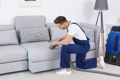 Male worker removing dirt from sofa. With professional vacuum cleaner indoors Stock Photos