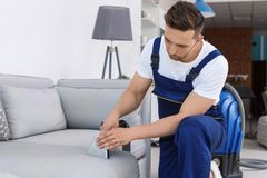 Male worker removing dirt from sofa with professional. Vacuum cleaner indoors Stock Photography