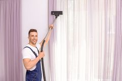 Male worker removing dust from curtains. With professional vacuum cleaner indoors Stock Photos