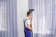 Male worker removing dust from curtains. With professional vacuum cleaner indoors Royalty Free Stock Image
