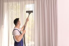 Male worker removing dust from curtains. With professional vacuum cleaner indoors Royalty Free Stock Images