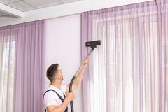 Male worker removing dust from curtains. With professional vacuum cleaner indoors Royalty Free Stock Photography