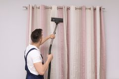 Male worker removing dust from curtains. With professional vacuum cleaner indoors Royalty Free Stock Photos