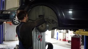 Male worker repairing automobile brake system at work. stock footage