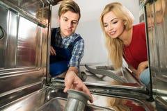 Male Worker Repairing Dishwasher In Kitchen Stock Photo