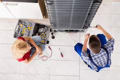 Male Worker Repairing Refrigerator In Kitchen Room. High Angle View Of Woman Looking At Male Worker Repairing Refrigerator In Kitchen Room Royalty Free Stock Photo