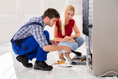 Male Worker Repairing Refrigerator In Kitchen Room. Woman Looking At Male Worker Repairing Refrigerator In Kitchen Room Stock Photo