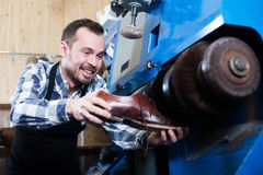 Male worker repairing shoe. Portrait of worker repairing shoe in specialized workshop Royalty Free Stock Images