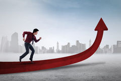 Male worker running on red arrow. Asian businessman running on upward red arrow to gain his goal, symbolizing business growth Royalty Free Stock Images